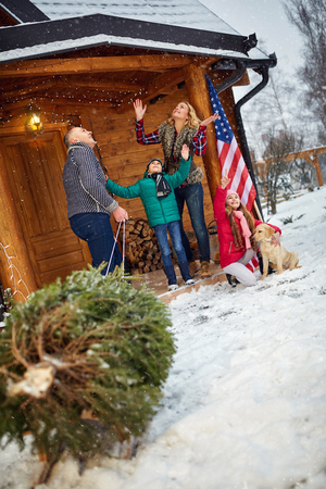 pappy: smiling family with Christmas tree on snowy day enjoying