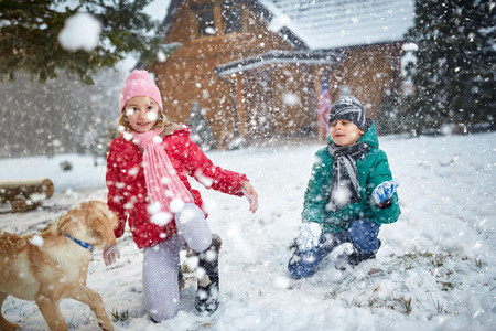 pappy: smiling children playing on snow with dog in winter holiday