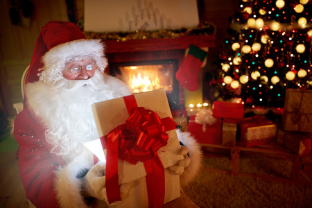 let out: Santa Claus opening a magic gift box and let out atmosphere of a Christmas
