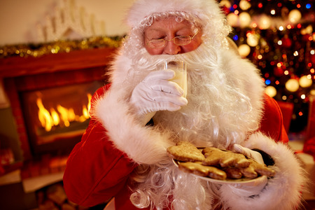 Real Santa Claus in warm room front of fire place eating Christmas traditional served food