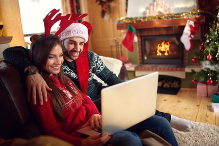 embraced: Embraced couple looking at laptop in decorated home for Christmas