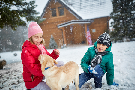 pappy: smiling children with dog playing on snow in winter holiday