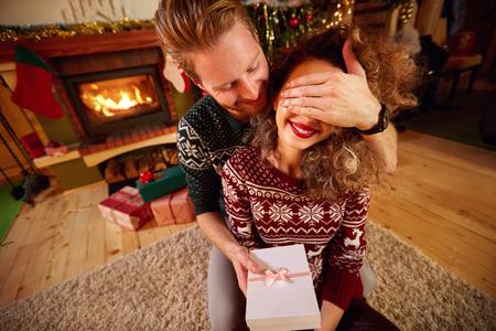 Man giving gift to girl as Christmas surprise Stock Photo