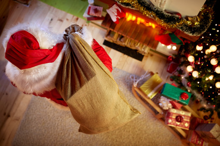 Santa Claus in room with big sack full of Christmas present, top view Stock Photo