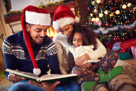fireplace family: Young afro family reading Christmas fairy tales near fireplace