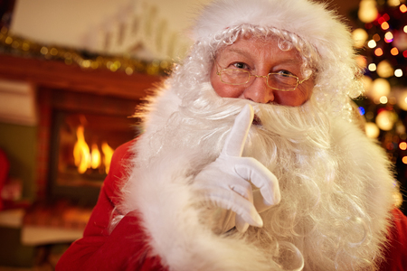 sh: Santa holding a finger to his mouth, silence for Christmastime Stock Photo