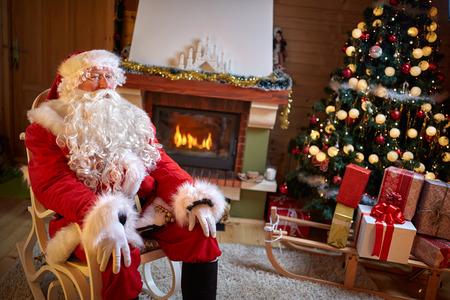 벽난로와 크리스마스 트리 장식 된 방에 앉아 산타 클로스 스톡 콘텐츠