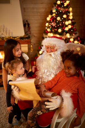 wish  list: Real Christmas father checking wish list surrounded with three cute girls different race