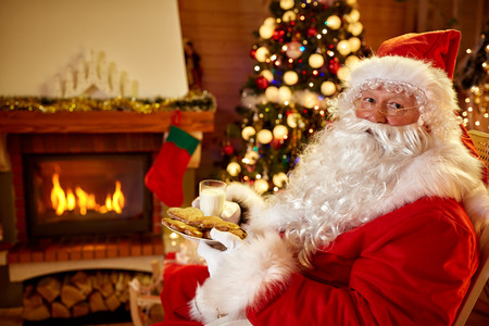 Santa Claus eats cookies and drinks milk near fireplace indoor