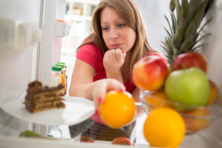whether: Attractive  female on diet in dilemma whether to eat piece of chocolate cake or orange from fridge