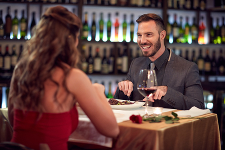 Smiling man with female celebrating anniversary in restaurant Stock Photo