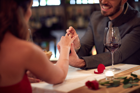 fingers put together: Man put ring on girlfriend's finger in restaurant