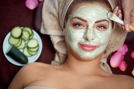 La piel sana requiere el cuidado, máscara natural en la cara de la mujer hermosa