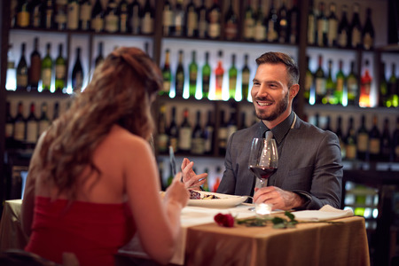 night out: Elegance man and woman talk and eat together inside