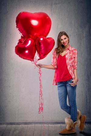 ragazza innamorata: Ragazza che tiene palloncini rossi luminosi. Donna sorridente in amore