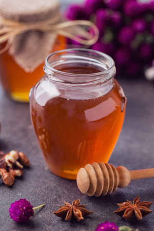 healthy honey in glass jar and dipper