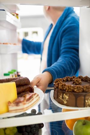 malos habitos: Individuo gordo toma plato lleno de comida dura altas calorías de la grasa refrigerador, hombre, coma,