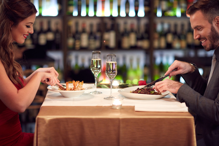 eat out: Woman and man eating good food in restaurant on evening