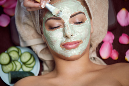 woman receiving spa treatment with cosmetic mask, skincare, antiaging, acne