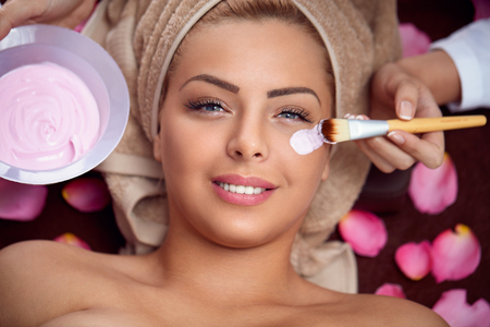 regeneration: beautician puts smiling girl a face mask in the salon