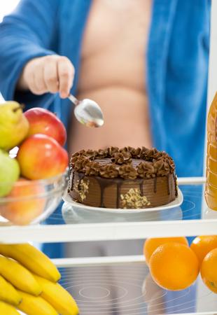 break the rules: Tasty big attractive cake in refrigerator is challenge for men on diet  diet, man, choc Stock Photo