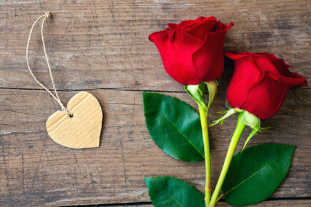 closeup view: close-up red roses and heart on wooden background top view Stock Photo