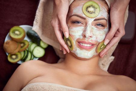 Maschera cosmetica naturale con cetriolo e kiwi sul volto di ragazza sorridente Archivio Fotografico - 70476587