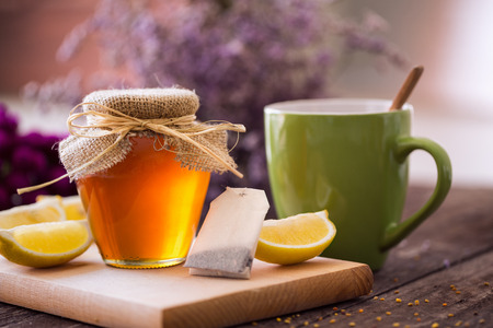 fresh hot cup of tea with honey and lemon background