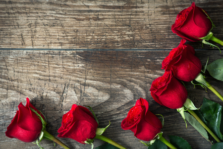 closeup view: close-up red roses on old wooden background. Top view