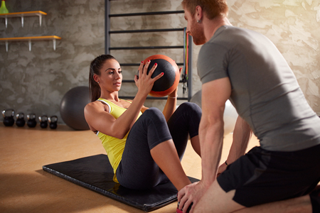 Girl exercises abs muscles using ball in fitness center