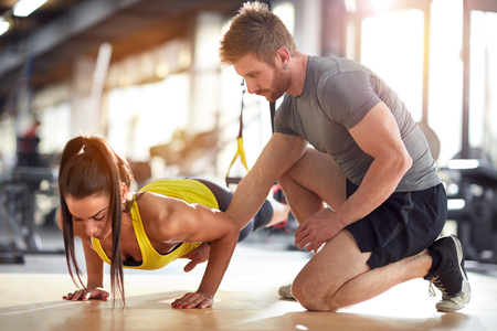 Fitness instructor on job with female athlete in gym Stockfoto