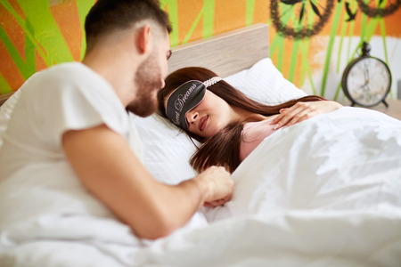 Man wakes up his girl with sleeping mask in the morning Stock Photo