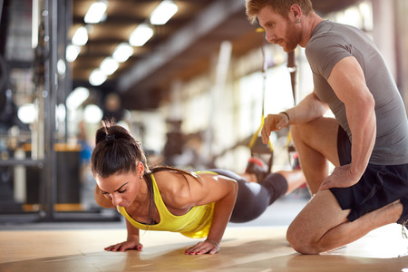 Fitness instructor with girl on training in fitness center Imagens