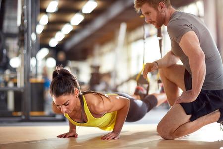 Fitnessinstruktör med flicka på träning i gym