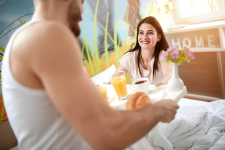Smiling girl takes tray with breakfast from boyfriend in bedroom