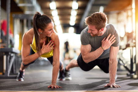 Man and woman strengthen hands at fitness training Stock Photo