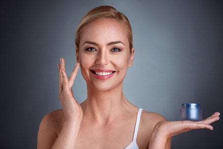 Smiling and satisfied woman applying cosmetic cream on face skin