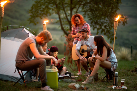 Group of young people at night in campground look at photos on mobile