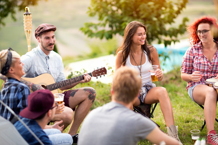 Cheerful guys and lassies enjoying and smiling in green wood Stock Photo