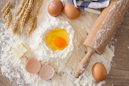 rollingpin: top view eggs, dough, flour and rolling-pin on wooden table background