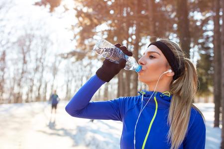 mujer deportista: Niña bebe agua en el entrenamiento de invierno al aire libre