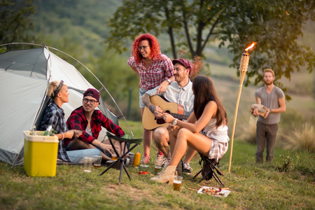Young males and females at music summer festival drink beer and play guitar in front of tent Stock Photo