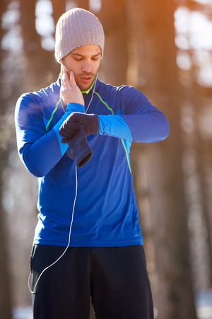 Male jogger controls heart beats on training outdoor