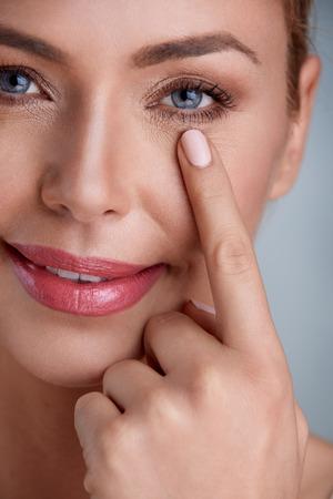 Woman holding finger on skin under eyes, checking wrinkles