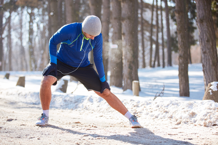 Jogger doing exercises in winter outdoor