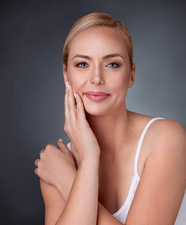 Mooie vrouw van middelbare leeftijd glimlachend kijken naar de camera aanraken haar wang, huidverzorging