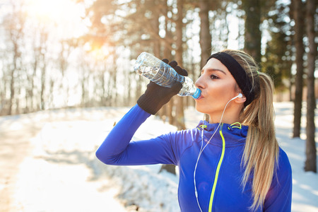Female drinks water on break from running in forest Stock Photo