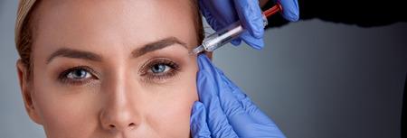 陽気な中年の女性はボトックス手順になって、医師は彼女の近くに立って、シリンジを保持していると女性の顔に触れる 写真素材