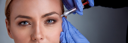 Cheerful middle age woman is getting botox procedure,  doctor is standing near her and holding syringe and touching to female face