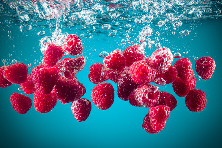 Fresh raspberries dropped into water background 版權商用圖片